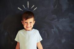反对惊叹号粉笔画的微笑的小男孩  免版税库存图片