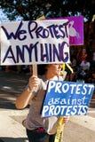 反对抗议的一个抗议者运载签到穿着或行为古怪的人迈阿密游行 免版税库存照片