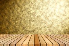 反对抽象金子纹理背景的透视棕色木地板与美丽的聚光灯散发作用 免版税库存照片