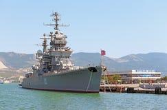 反对新罗西斯克小游艇船坞的巡洋舰  免版税库存照片