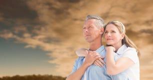 反对日落云彩的愉快的夫妇 免版税库存图片