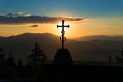 反对日落和小山的基督徒十字架在背景 免版税库存照片