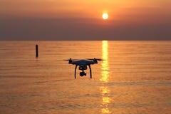 反对日落天空的寄生虫飞行 库存图片