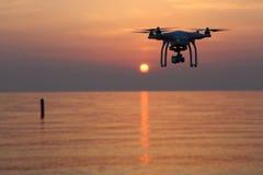反对日落天空的寄生虫飞行 免版税库存图片