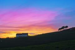 反对日落天空的谷仓和树剪影 免版税库存图片