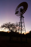 反对日落天空的风车 库存图片
