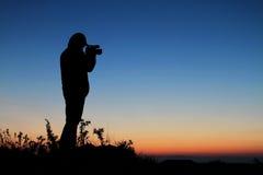 反对日落的剪影摄影师 免版税库存图片