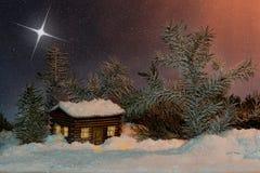 反对日落的圣诞节星在雪和冷杉的房子 库存照片