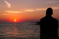 反对日落的渔夫在海 库存照片