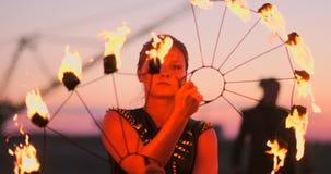 反对日落的火舞蹈家 在她的舞蹈表现期间,年轻女人摆在与她的火箍反对日落 股票录像