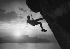 反对日落的登山人 黑色白色 库存照片