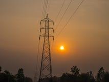 反对日落背景的高压塔 库存照片