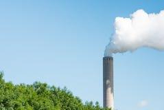 反对明亮的蓝天的抽烟的烟囱 图库摄影