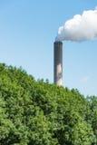 反对明亮的蓝天的抽烟的烟囱 免版税库存图片