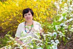 反对春天风景的妇女 免版税图库摄影