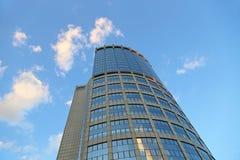 反对晚上天空的办公室现代大厦与白色云彩 库存照片