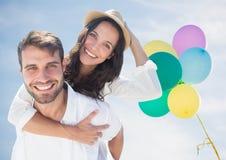 反对晴朗的天空和baloons的千福年的夫妇肩扛 库存照片
