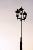 反对暮色背景的老街道路灯柱 免版税库存照片