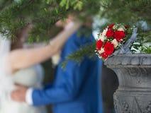 反对最近被婚姻的夫妇的新娘花束 免版税库存图片