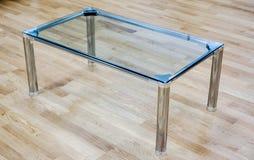 反对木地板的清楚的玻璃小桌在办公室招待会 免版税库存照片
