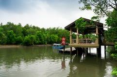 反对木客舱的小船相接与在马来语的一个标志 免版税库存图片