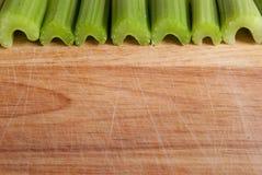 反对木头的芹菜茎 免版税库存照片