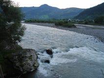 反对村庄房子背景的快速,快速河流程在一座大山的脚 库存图片