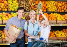 反对果子架子的愉快的家庭有购物 免版税库存照片
