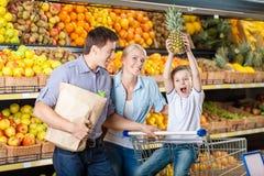 反对果子架子的年轻家庭有购物 免版税图库摄影