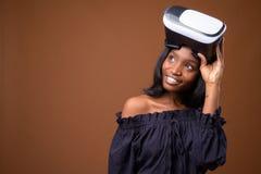 反对棕色背景的年轻美丽的非洲祖鲁族人妇女 免版税库存照片