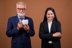 反对棕色背景的成熟不同种族的企业夫妇 免版税库存照片