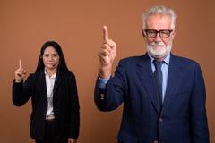 反对棕色背景的成熟不同种族的企业夫妇 免版税库存图片
