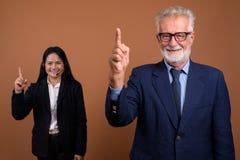 反对棕色背景的成熟不同种族的企业夫妇 免版税图库摄影