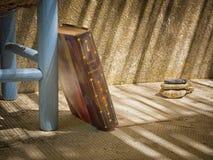 反对椅子的旧书 免版税库存照片