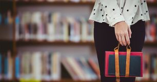 反对模糊的书架的大学生下体 免版税图库摄影