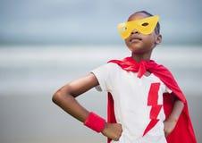 反对模糊的海滩的女孩超级英雄 免版税库存图片