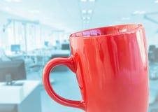 反对模糊的蓝色办公室的红色咖啡杯 免版税图库摄影