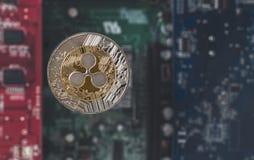 反对模糊的集成电路背景的金银色波纹硬币 免版税库存照片