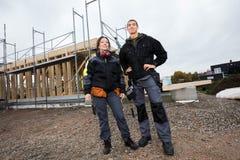 反对残缺不全的大厦的男性和女性木匠 库存图片