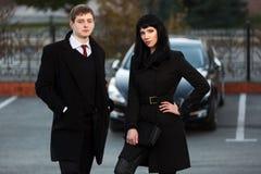 反对汽车停车处的年轻企业夫妇 库存照片