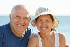 反对海和天空的快乐的成熟夫妇 免版税图库摄影