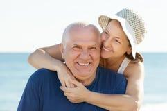 反对海和天空的愉快的成熟夫妇 免版税库存照片