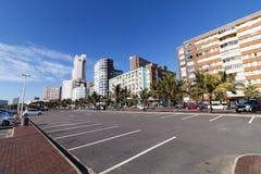 反对海滩前的城市地平线的空的停车区域 库存照片