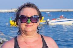 反对海的妇女佩带的太阳镜 图库摄影