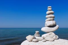 反对海的平衡和世故石头 在蓝天背景的白色岩石禅宗  库存图片