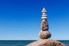 反对海的平衡和世故石头 晃动在蓝天背景的禅宗  免版税库存照片