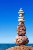 反对海的平衡和世故石头 晃动在蓝天背景的禅宗  免版税图库摄影