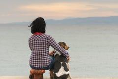 反对海观看日落的妇女和她的狗 免版税库存图片