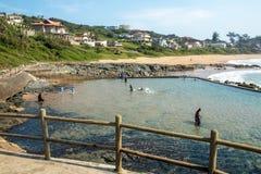反对海滩和沿海居民住房土地的潮汐水池 免版税库存图片