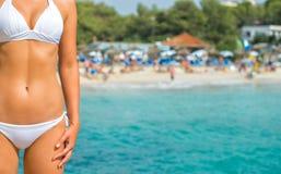 反对海滩的妇女身体 免版税库存图片